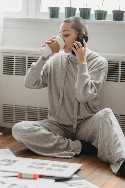 Female with short hair in pajamas sipping coffee and talking on phone while sitting on floor near window