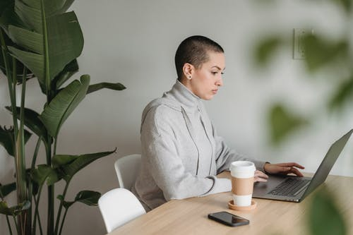 Side view of concentrated female freelancer in casual clothes sitting at table with laptop and cup of coffee near plants