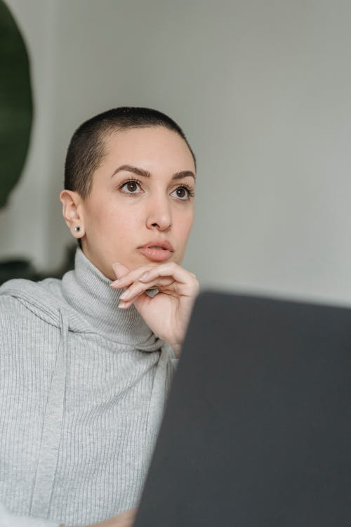Thoughtful short haired woman with laptop