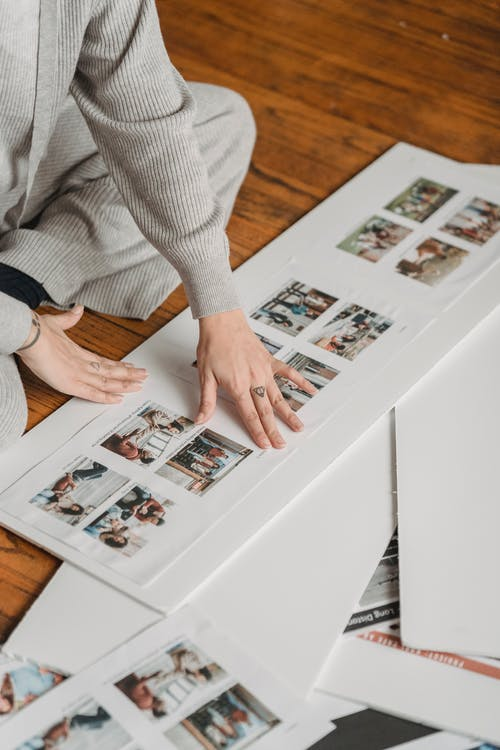 Crop person gluing family photos to poster