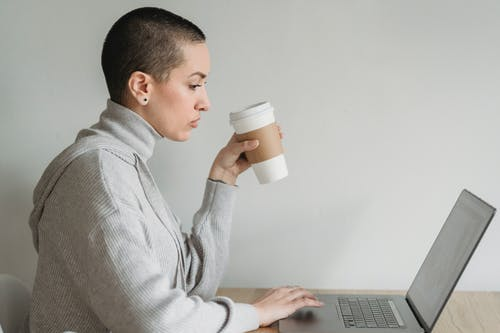 Side view of concentrated female in casual clothes sitting with laptop at table while drinking coffee