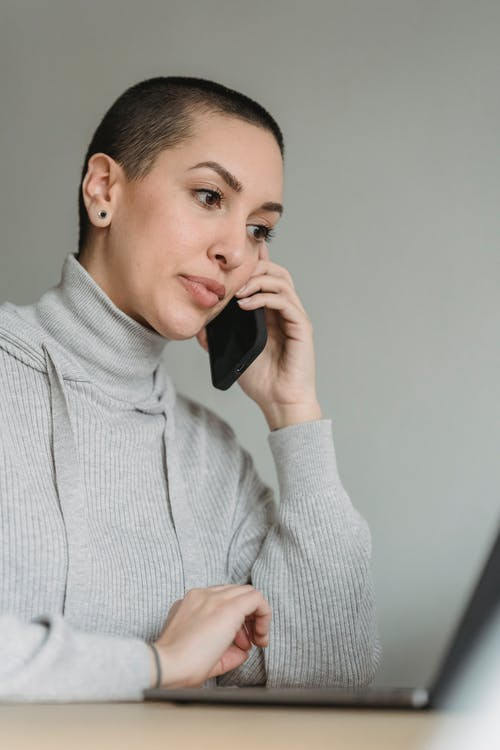 Thoughtful woman talking on smartphone and working on laptop