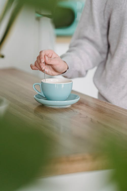Crop anonymous female in gray sweater stirring sugar in cup of freshly brewed coffee while standing near kitchen counter