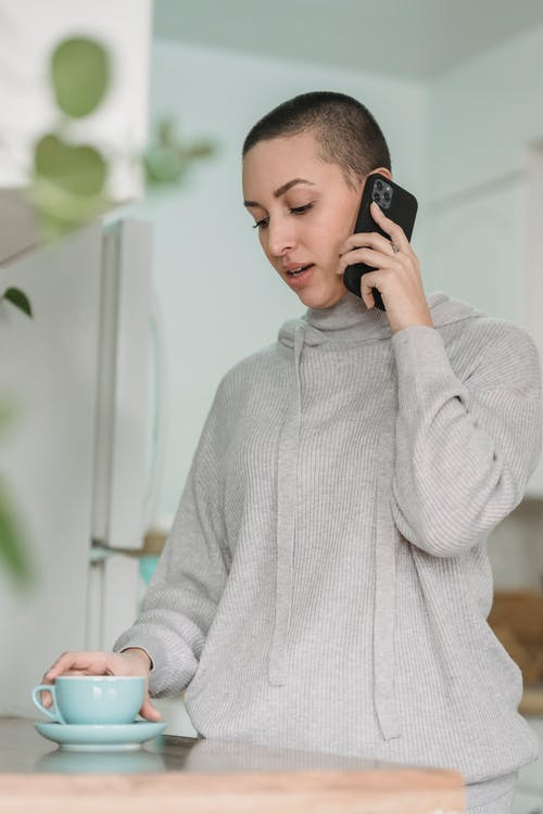 Young woman speaking on smartphone in kitchen