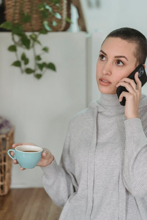 Thoughtful young female in gray domestic clothes having conversation via cellphone and enjoying hot drink in light room