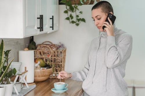Calm young female in domestic wear having conversation on mobile phone and stirring coffee while standing in contemporary light kitchen