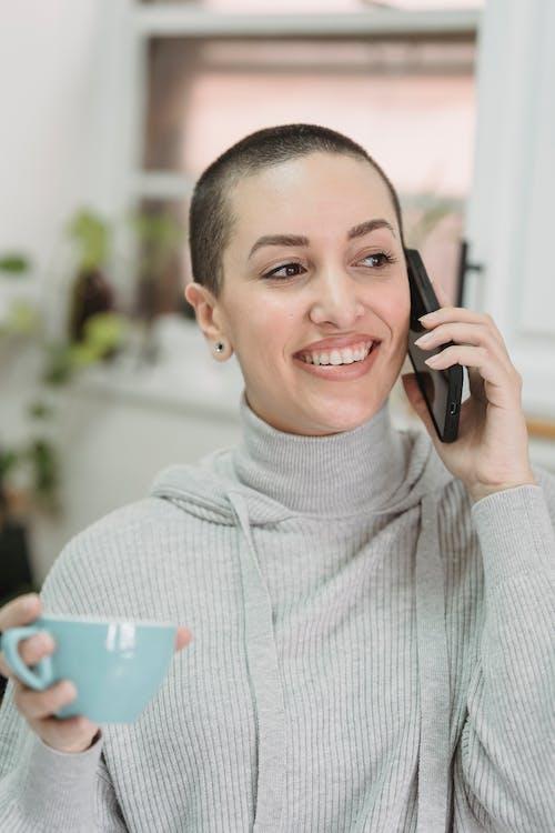 Happy woman talking on smartphone in kitchen