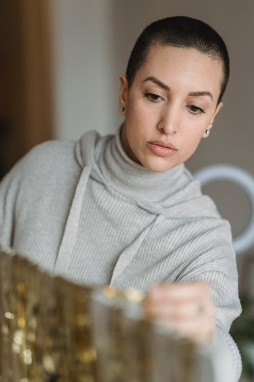 Young contemplative female with short hair hanging shiny golden tinsel on white stand
