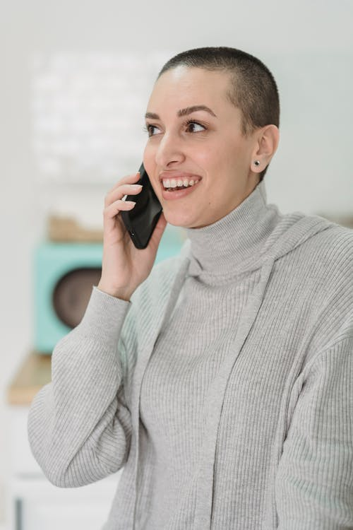 Cheerful woman with short hair talking on smartphone indoors