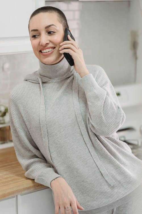 Pondering woman talking on smartphone at home