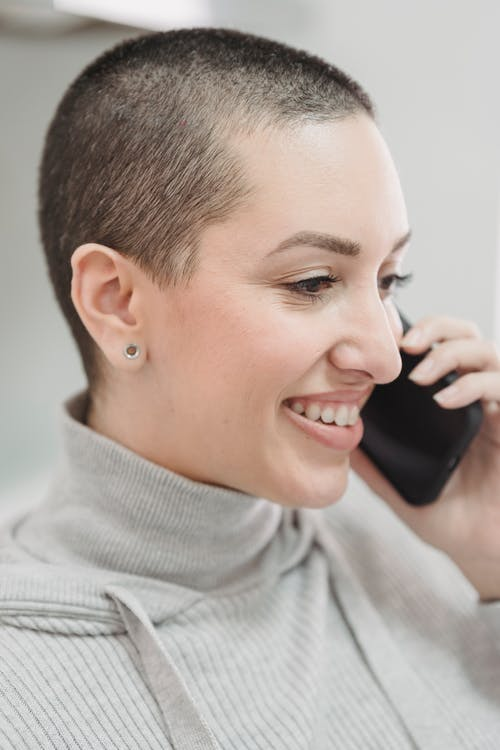 Smiling woman with short hair conversing on smartphone