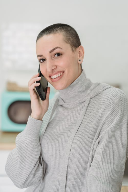 Sincere woman with short hair speaking on smartphone indoors