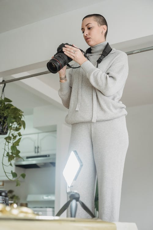 From below of young woman taking photo on professional camera against glowing lamp on table at home