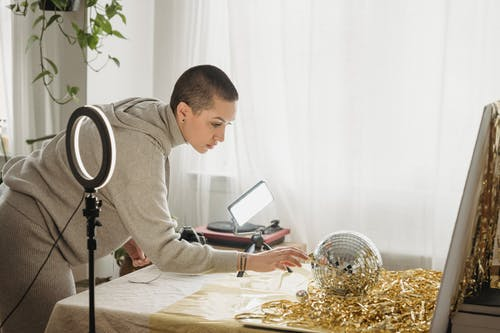 Focused woman preparing disco ball and tinsel for photo session
