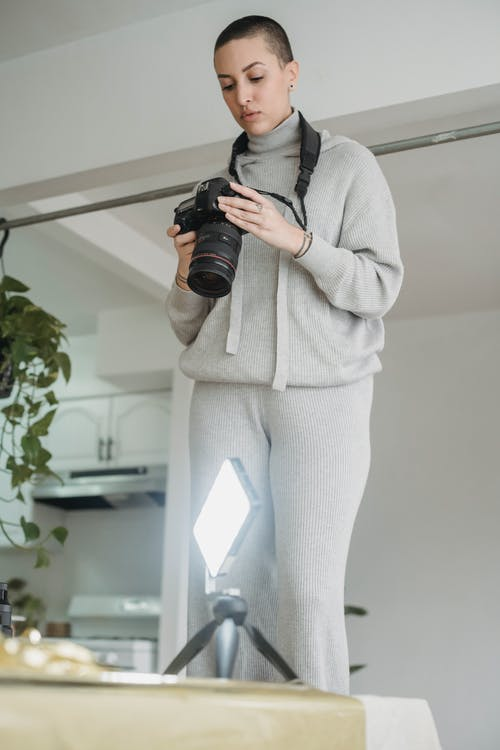 Photographer setting up photo camera for shooting