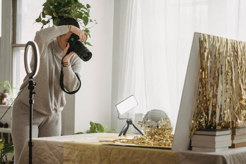 Female photographer with short hair standing at table with shimmering tinsel and party ball near luminous lamp on tripod