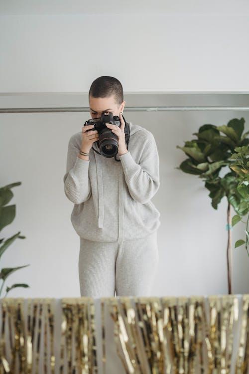 Photographer taking photos on camera in light studio