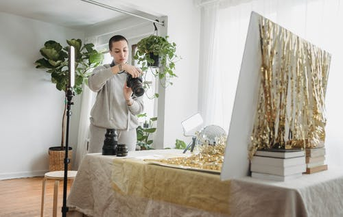 Serious woman reviewing pictures on photo camera while standing near table with golden tinsel and party ball