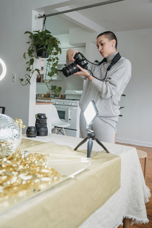 Low angle of concentrated professional photographer checking photos on camera while shooting disco ball and golden tinsel