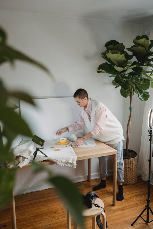 Photographer at table with cup of coffee and fabrics indoors