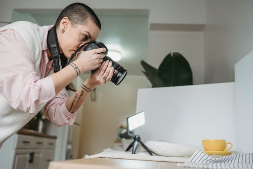 Side view of tattooed woman taking photo of yellow cup on digital camera against table with glowing lamp at home