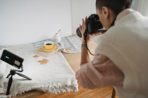 Crop photographer taking photo of coffee on camera in house