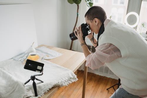 Side view of tattooed female taking photo of hot beverage on professional camera between lamps at home