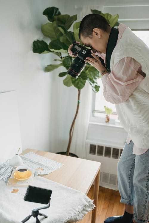 Photographer taking photo of coffee on professional camera in room