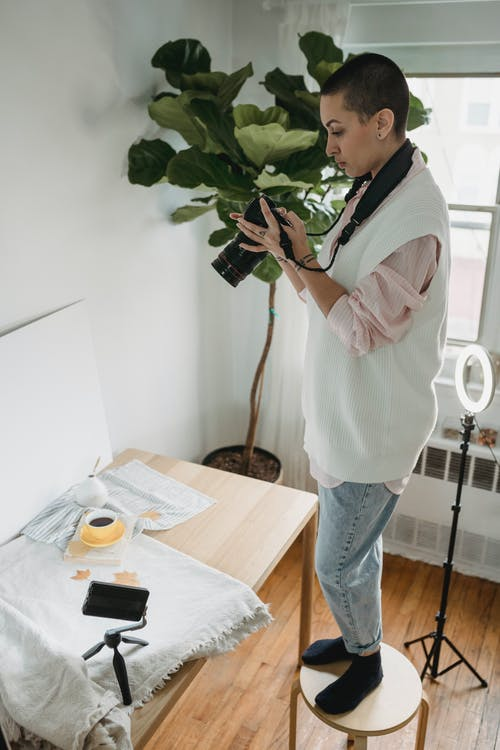 Photographer taking photo of coffee on camera in house