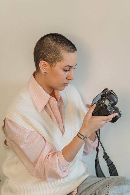 Focused woman using photo camera in studio