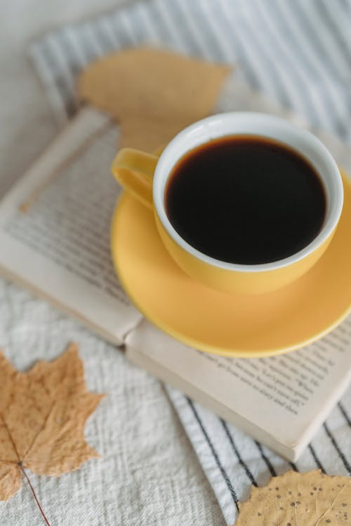 From above freshly brewed black coffee in yellow cup placed on opened book in light room