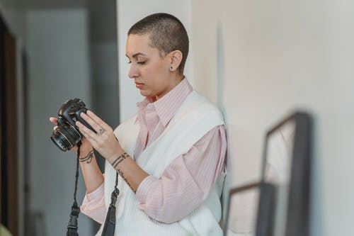 Concentrated young female with short hair looking through pictures in professional photo camera in light studio