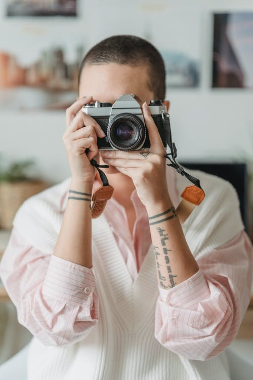 Woman taking photos on professional camera at home