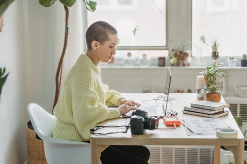 Side view of concentrated female with short hair editing photos on netbook while sitting at table with photo camera in light room