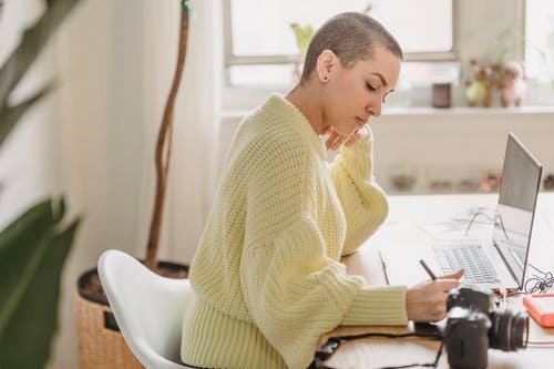 Side view of serious female with short hair drawing with stylus while editing photos at table with photo camera during work in room with green plant