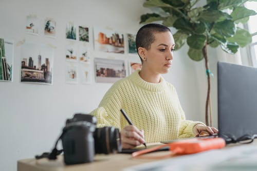 Focused woman drawing on graphic tablet while editing photos