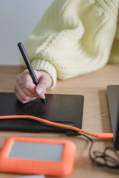 Anonymous woman writing on graphic tablet