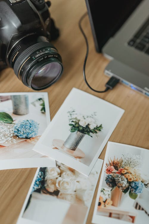 Printed photos on table with photo camera