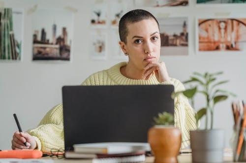 Serious female with short hair looking at camera while drawing with stylus at table with netbook and small potted plants