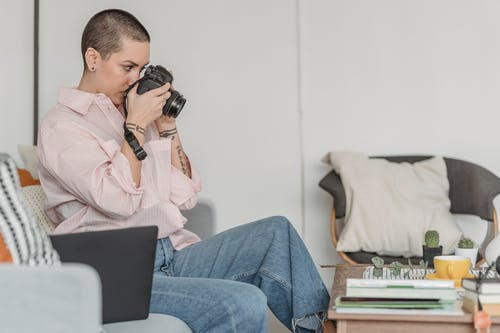 Side view of concentrated female photographer with short hair taking picture of composition of tea and green twig on table