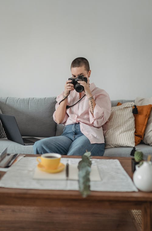 Anonymous photographer taking photo of composition on table