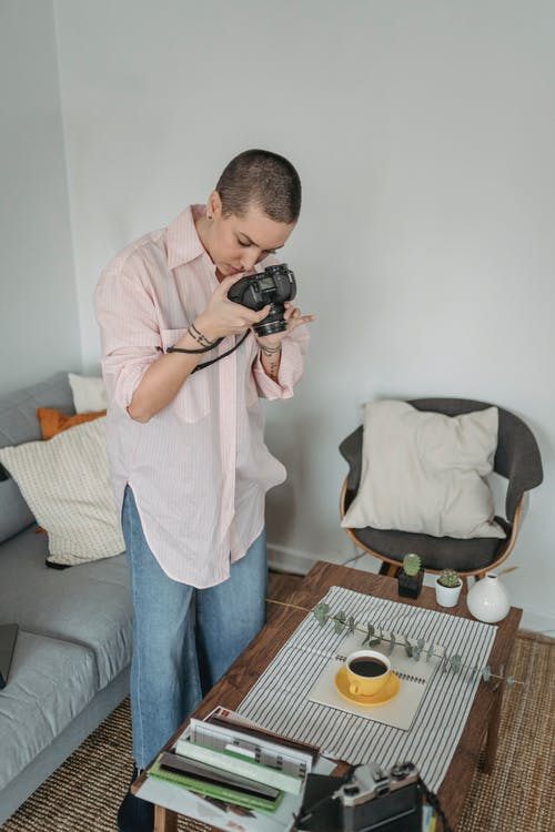 Focused female photographer with photo camera taking picture of cup with tea and green twig arranged on table in light room