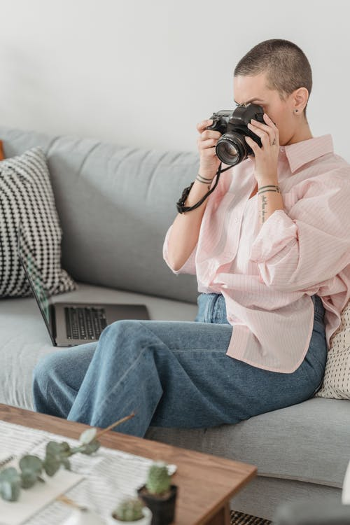 Anonymous woman on couch taking photo on photo camera