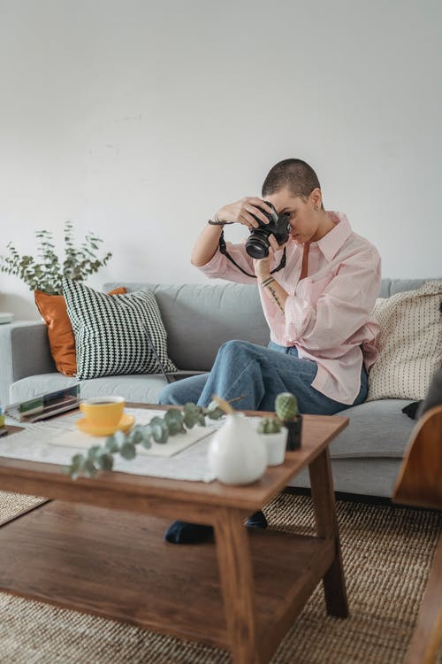 Focused woman taking photo of green twig with cup of tea