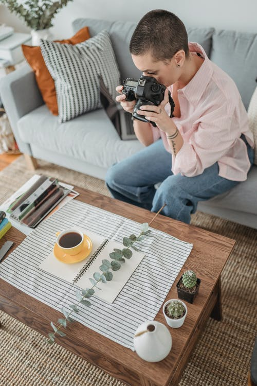Woman taking photos of cup with coffee on photo camera