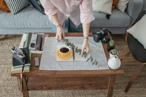 Crop faceless woman arranging coffee and twig on table
