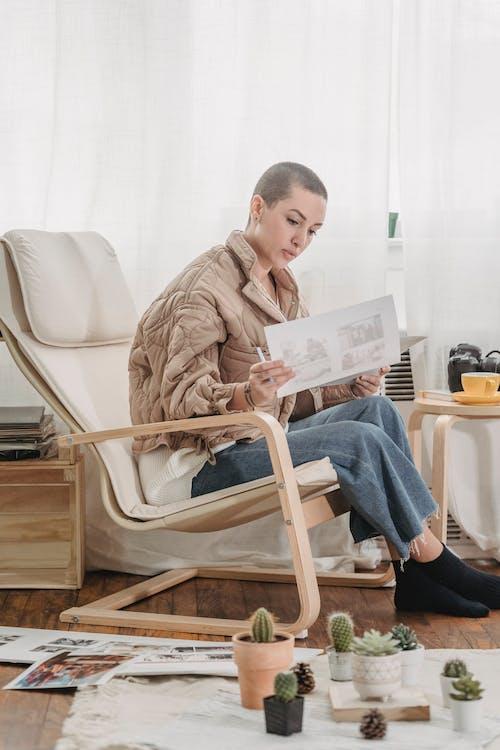 Woman reading documents on chair near cacti arranged on floor