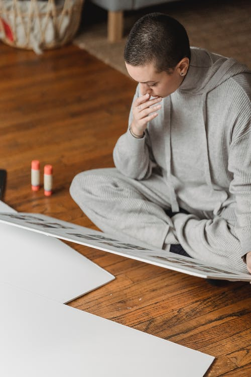 Thoughtful woman looking at photo collage on floor