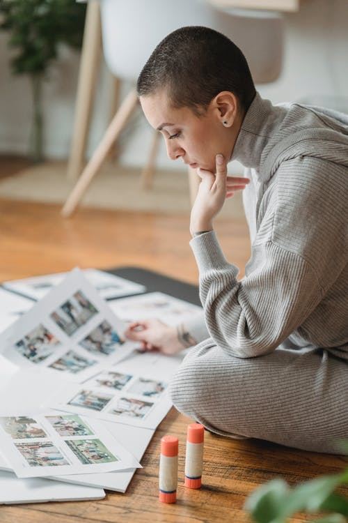 Contemplative woman looking at printed photos on floor