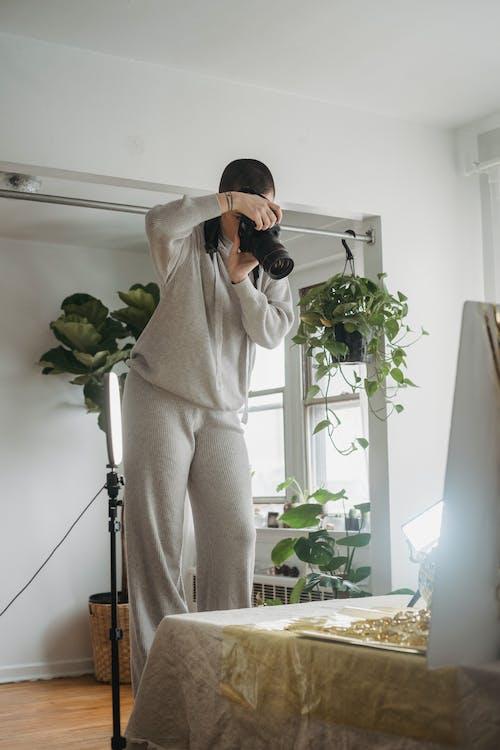 Faceless woman taking photos in studio